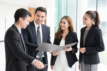 Group of business people discussing work in building corridor Stock Photo
