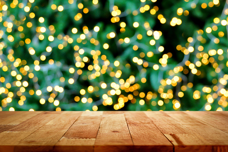 new year counter: Wood table top with bokeh from decorative light on christmas tree in background