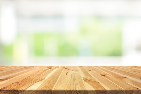 Wood table top on blur white green background from kitchen window - can be used for display or montage your products (or foods) Stockfoto