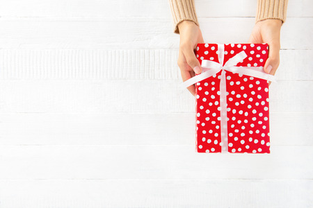 box: Woman hands giving red gift box on white wood panel background with copy space