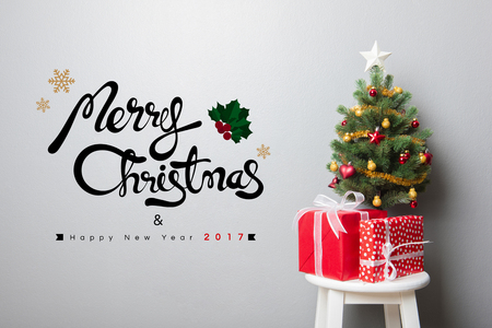 red gift box: Gift boxes and small decorated Christmas tree on the chair with MERRY CHRISTMAS and HAPPY NEW YEAR 2017 text on the wall Stock Photo