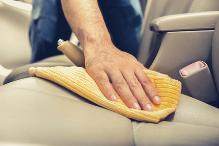 detailing: A man cleaning leather car seat with microfiber cloth - auto detailing and valeting concept Stock Photo