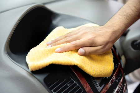 valeting: A man hand cleaning car interior with microfiber cloth - car detailing and valeting concept Stock Photo