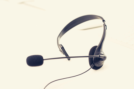 telemarketing: Microphone headset on the table, vintage tone effect - call center,customer service and telemarketing concepts