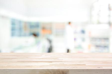 Lege houten tafelblad op de achtergrond van de wazige apotheek (chemicus of cosmetische winkel)