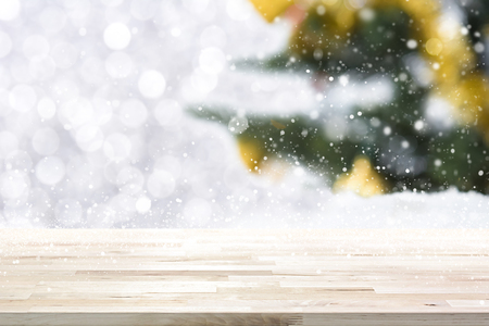top of the year: Wood table top on abstract white bokeh and blur Christmas tree background in winter snowfall - can be use for display and montage your products