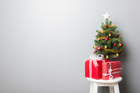 gift boxes and small decorated christmas tree on gray wall background stock photo 65692354