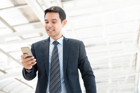 Handsome Asian businessman using smartphone