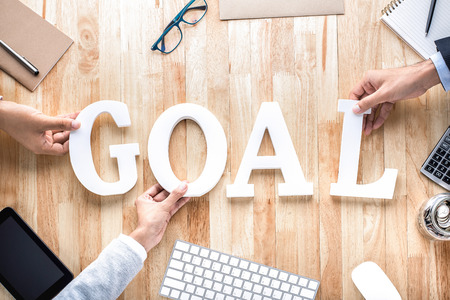 business letters: Business people hands arranging letters GOAL on working table -goal setting concept