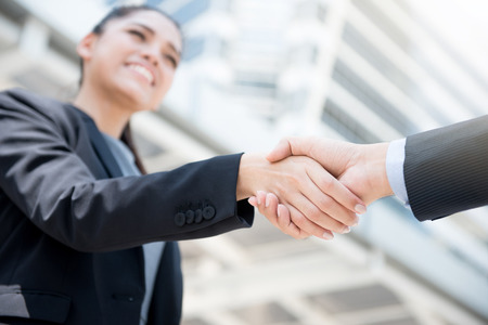 Businesswoman making handshake with a businessman -greeting, dealing, merger and acquisition concepts Stock Photo