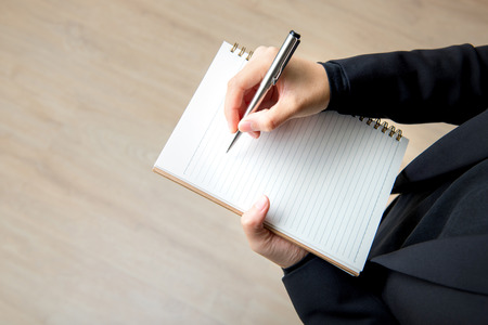 jot: Businesswoman hand writing on blank notebook with pen Stock Photo