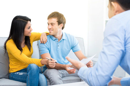 interracial relationships: Young interracial couple meeting with consultant (or counselor, financial adviser, real estate agent etc.)