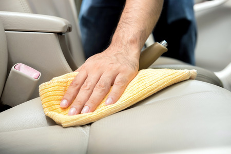 valeting: A man cleaning leather car seat with microfiber cloth - auto detailing and valeting concept Stock Photo