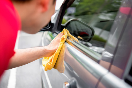 valeting: A man cleaning car with microfiber cloth  - auto detailing and valeting concept