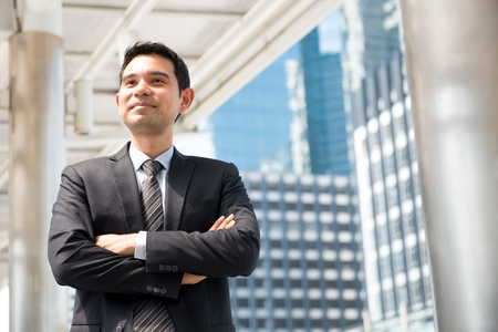 business asia: Asian businessman standing and crossing his arms in blur building background