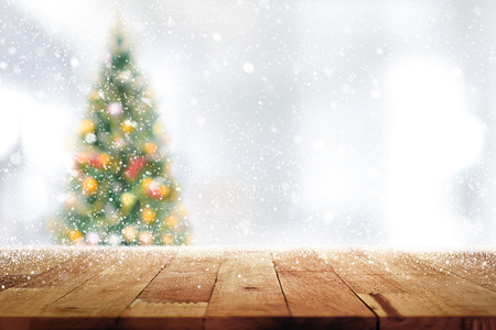 Wood table top on blur Christmas tree  in snowfall background - can be used for display or mantage your products