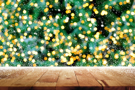 top of the year: Wood table top with bokeh from decorative light on christmas tree and snow in background
