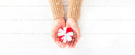 red gift box: Woman hands giving small red gift box on white wood background with snowfall, panoramic banner Stock Photo