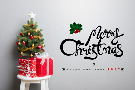 gift boxes and small decorated christmas tree on stool chair with merry christmas and happy new