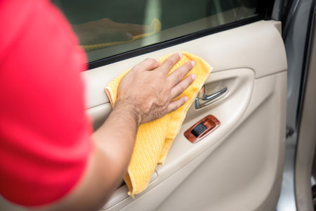 valeting: Auto service staff cleaning car door interior panel with microfiber cloth - car detailing and valeting concept Stock Photo