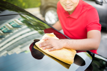 valeting: Auto service staff cleaning car rear windshield with microfiber cloth - car detailng and valeting concept