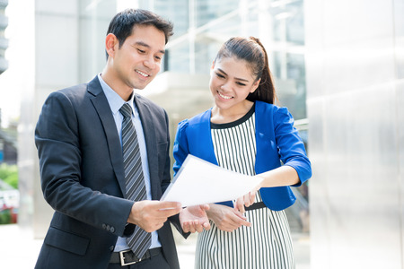 Business people discussing document while walking outdoors in front of office building Imagens - 66038436