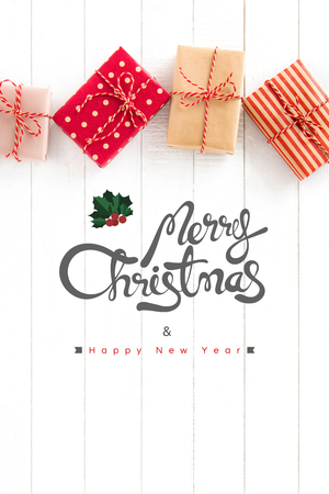 text year: Merry Christmas and Happy New Year text with gift boxes on white wood background, top view