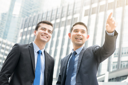 out of business: Two businessmen standing outdoors in the city with one hand pointing out - business partner and co-worker concepts