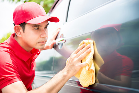 valeting: Male worker cleaning and looking at car door seriously - auto detailing and valeting concept Stock Photo