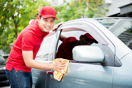 Worker in red uniform cleaning car - auto detailing and valeting, service concepts