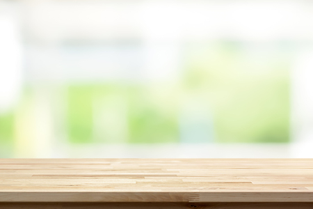 Wood table top on blur white green kitchen window background - can be used for display or montage your products (or foods)