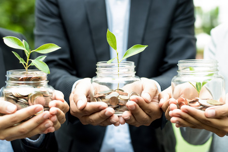 business money: Business people holding glass jars with plants growing from money - investment and financial metaphor