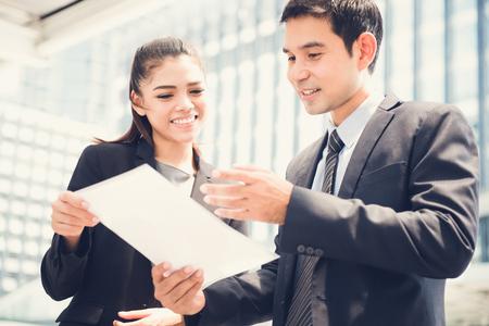 Asiática de negocios y hombre de negocios examinar el documento al aire libre Foto de archivo - 66465257