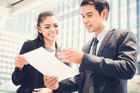 Aziatische zakenvrouw en zakenman bespreken document buitenshuis
