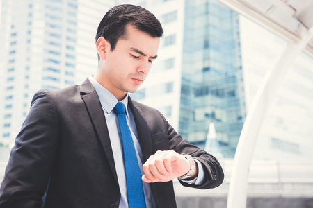 checking time: Businessman looking at his watch checking time with serious face Stock Photo