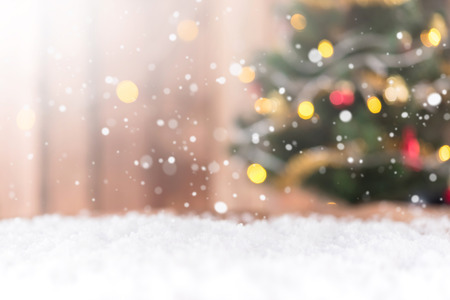 chritmas: Snow background with blur bokeh of decorated Chritmas tree Stock Photo