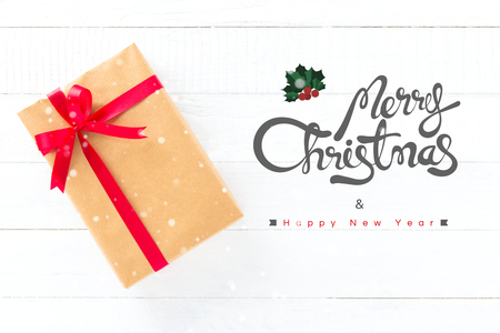 text year: Merry Christmas and Happy New Year text with gift box on white wood background