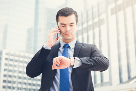 look latino: Businessman looking at his watch checking time while calling on cell phone in blur office building background