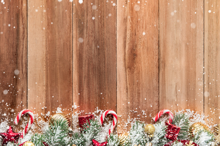 Christmas ornaments with snow on wood background, top view, border design