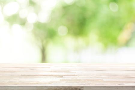 Holztischplatte auf Unschärfe grünen Hintergrund der Bäume im Park - kann zur Anzeige oder montage Ihrer Produkte verwendet werden, Standard-Bild