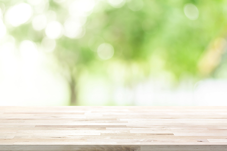 Wood table top on blur green background of trees in the park - can be used for display or montage your products