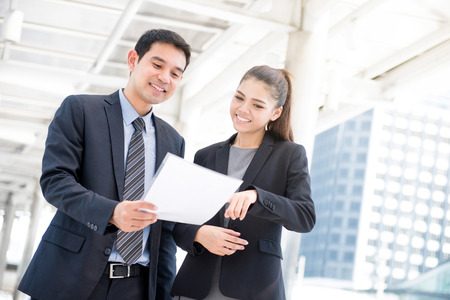 Businessman and businesswoman discussing document in outdoor walkway