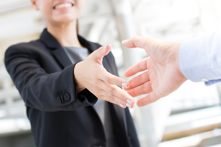 Giovane imprenditrice di andare a fare stretta di mano con un uomo d'affari -greeting, che si occupa, di fusione e acquisizione concetti Archivio Fotografico