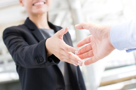 Jeune femme d'affaires va faire poignée de main avec un homme d'affaires Accueil des voyageurs, traitant, fusions et acquisitions concepts Banque d'images
