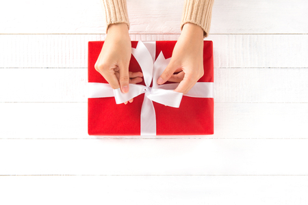 red box: Hands tying ribbon on red gift box, top view