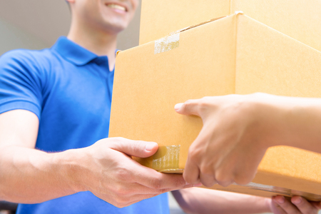 Delivery man in blue uniform handing parcel boxes to recipient - courier service concept Stock Photo