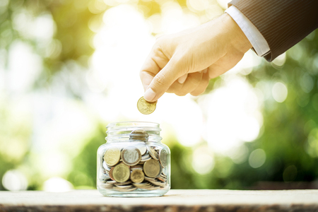 invest: Businessman hand putting money (coin) into the glass jar - savings, investment and donation concepts