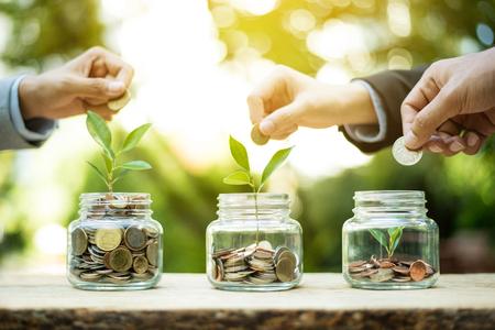 Zakenmanhanden die geld (muntstuk) zetten in de glaskruik - besparingen en investeringsconcept Stockfoto