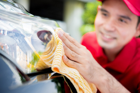 A man cleaning car headlight - car detailing and valeting concept
