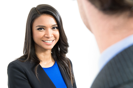 Asian businesswoman smiling and looking at a businessman
